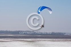 Aerial view of paramotor flying over the vastness of winter snow