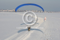 Aerial view of paramotor following a road in winter in France