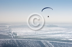 paramotor seen from the sky in France flying over snowy fields i